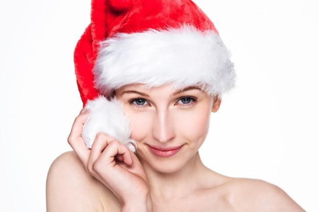 Pięknej kobiety szczęśliwi boże narodzenia w santa kapeluszu na bielu