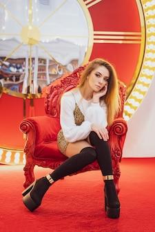 Pięknej kobiety uśmiechnięty bożenarodzeniowy trybowy obsiadanie na czerwonym krześle