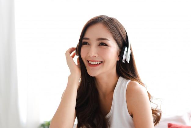 Pięknej młodej azjatykciej kobiety relaksujący słuchanie muzyka z hełmofonami na łóżku w domu