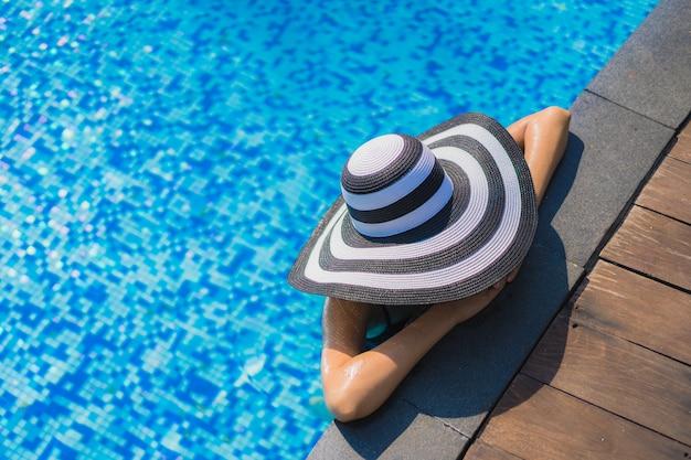Pięknej młodej azjatykciej kobiety szczęśliwy uśmiech i relaksuje w pływackim basenie