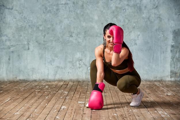 Pięknej młodej dziewczyny bokserskie rękawiczki blisko ściany.
