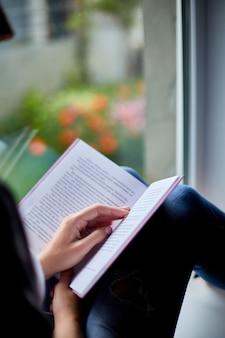 Pięknej młodej kobiety czytelnicza książka blisko okno w domu.