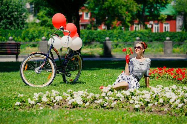 Pięknej młodej kobiety szpilki retro styl z bicyklem