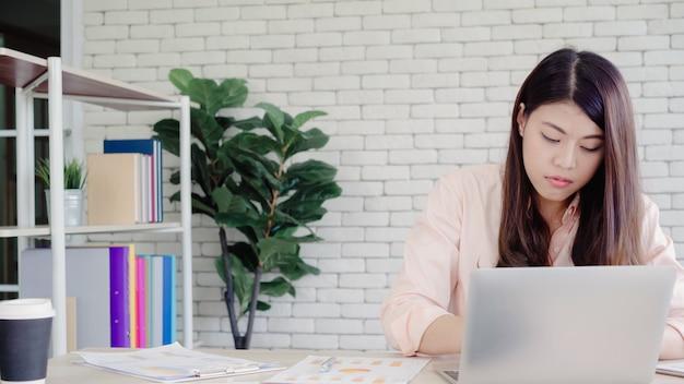 Pięknej młodej uśmiechniętej azjatykciej kobiety pracujący laptop na biurku w żywym pokoju w domu.