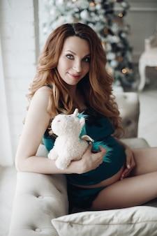Pięknej mody ciążowa młoda kobieta w piżamach pozuje na kanapie