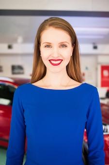 Pięknej mody europejski młody blondynki kobiety obsiadanie w czerwonym samochodzie ubierał w błękit długiej sukni