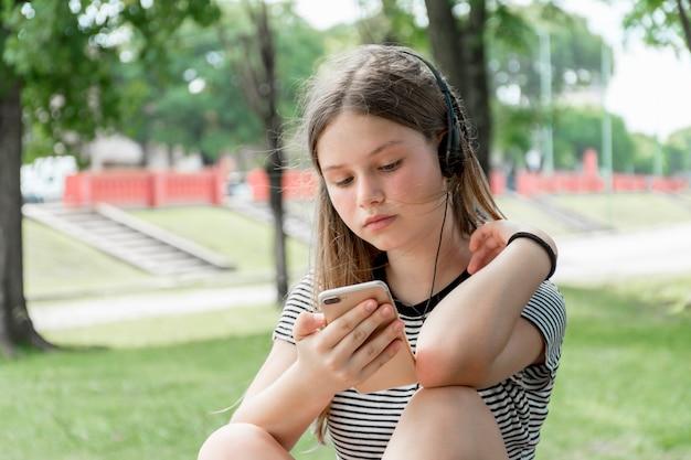Pięknej nastoletniej dziewczyny słuchająca muzyka podczas gdy używać telefon komórkowego przy parkiem