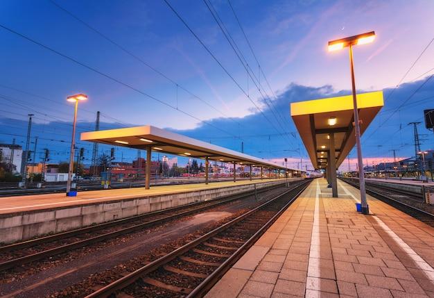 Pięknej nocy przemysłowy krajobraz, nowożytna stacja kolejowa w nuremberg, niemcy. platformy kolejowej na tle niebieskiego nieba
