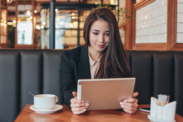 Pięknej powabnej brunetki uśmiechnięta azjatycka dziewczyna z pastylką przy stołem w kawiarni