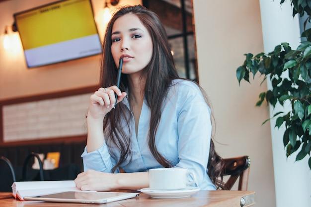 Pięknej powabnej brunetki uśmiechnięty azjatycki dziewczyny działanie lub studiowanie przy stołem w kawiarni