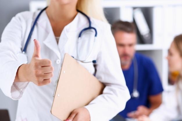 Pięknej uśmiechniętej kobiety doktorski pokazuje ok lub potwierdza znaka