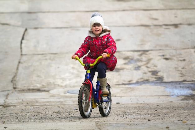 Pięknej uśmiechniętej małej dziewczynki jeździecki bicykl w parku