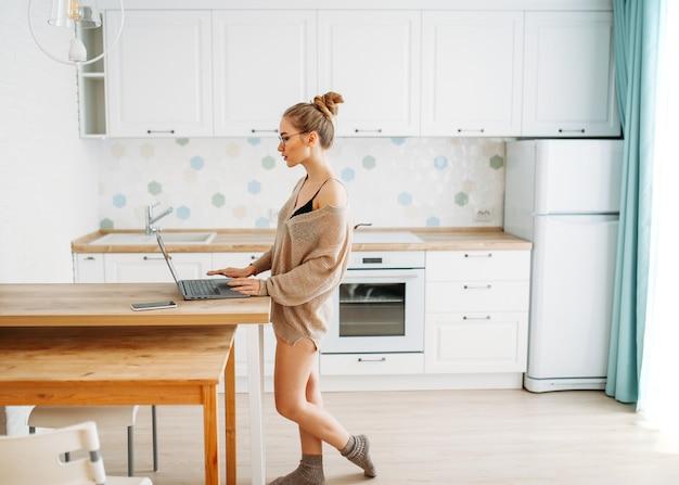 Pięknej uśmiechniętej młodej kobiety uczciwa długie włosy dziewczyna jest ubranym w wygodnym trykotowym pulowerze w szkłach używać laptop przy jaskrawą kuchnią