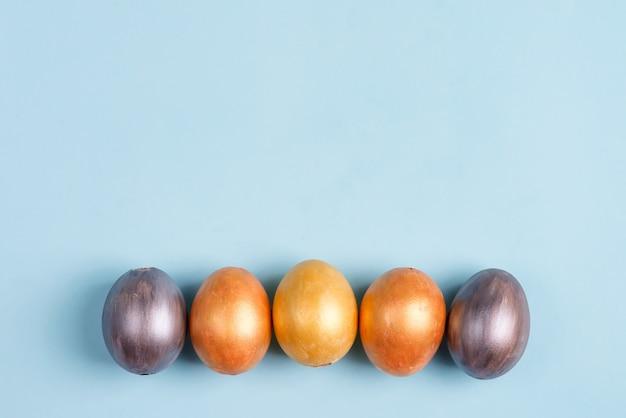 Pięknej wielkanocy srebni i złociści jajka na błękitnym tle z kopii przestrzenią