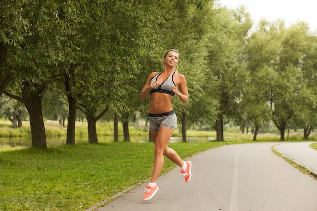 Pięknej zdrowej sprawności fizycznej blond kobieta w moda sporta odzieży bieg i ćwiczy joga w parku przy zmierzchem