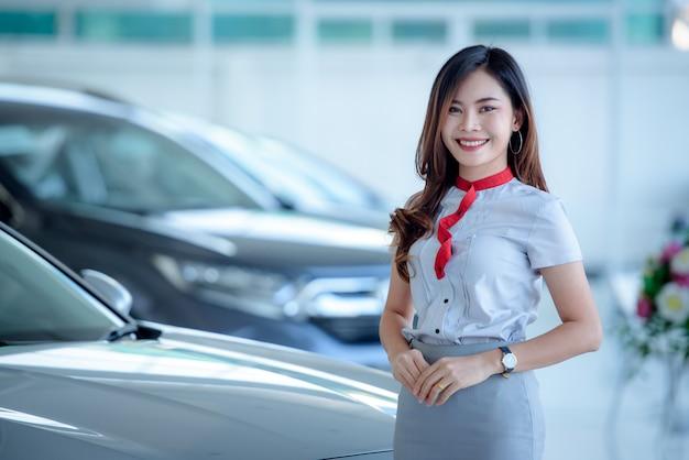 Piękni azjatyccy sprzedawcy chętnie sprzedają nowe samochody w salonie i zachęcają klientów do kupowania samochodów u dealerów samochodowych.