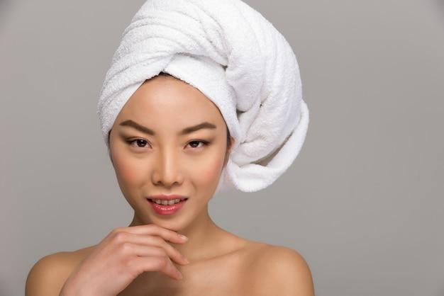 Piękni azjatykci kobiety piękna portrety. chińska dziewczyna stoi przed lustrem i dba o jej wygląd.