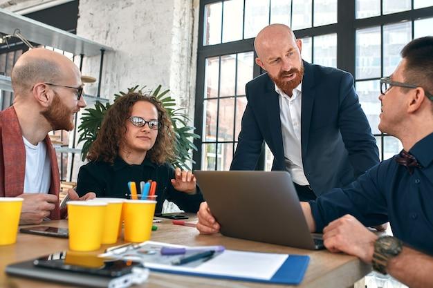 Piękni biznesmeni używają gadżetów, rozmawiają i uśmiechają się podczas konferencji w biurze. selektywna ostrość