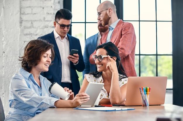 Piękni biznesmeni używają gadżetów, rozmawiają i uśmiechają się podczas konferencji w biurze
