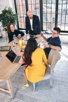 Piękni biznesmeni używają gadżetów, rozmawiając i uśmiechając się podczas konferencji w biurze.