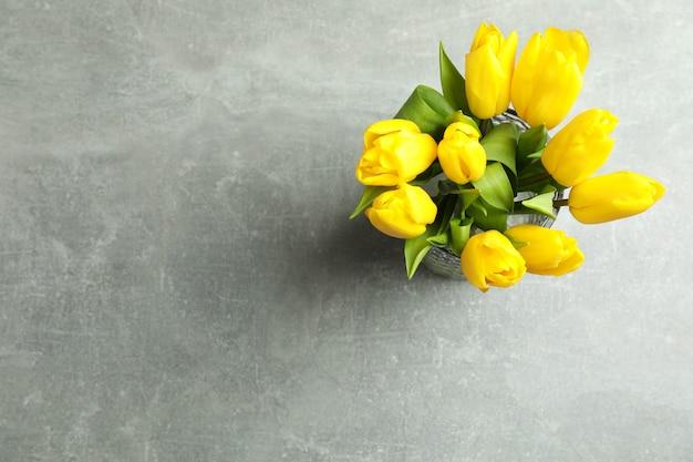 Piękni bukietów tulipany w wazie na szarość, odgórny widok. miejsce na tekst