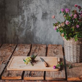 Piękni bukiety wildflowers drewnianego stołu zimna betonowa ściana.