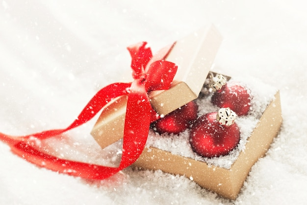 Piękni czerwoni klasyczni baubles lub boże narodzenie dekoracja w prezenta pudełku z śniegiem
