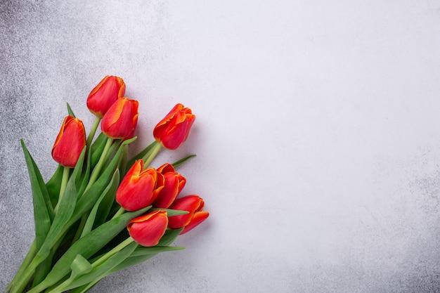 Piękni czerwoni tulipany na lekkim kamienia stole. tło wiosna. widok z góry. skopiuj miejsce