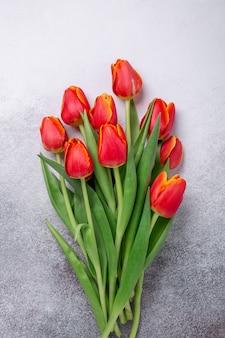 Piękni czerwoni tulipany na lekkim kamienia stole.