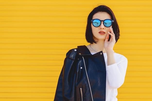 Piękni dziewczyna okulary przeciwsłoneczni na jaskrawym żółtym tle
