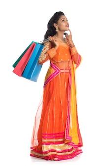 Piękni indiańscy młodej kobiety mienia torba na zakupy podczas gdy będący ubranym tradycyjną etniczną odzież. pojedynczo na białej ścianie