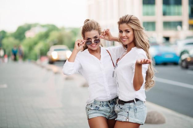 Piękni kobieta bliźniacy pokazuje pokój i emocjonalnie pozuje