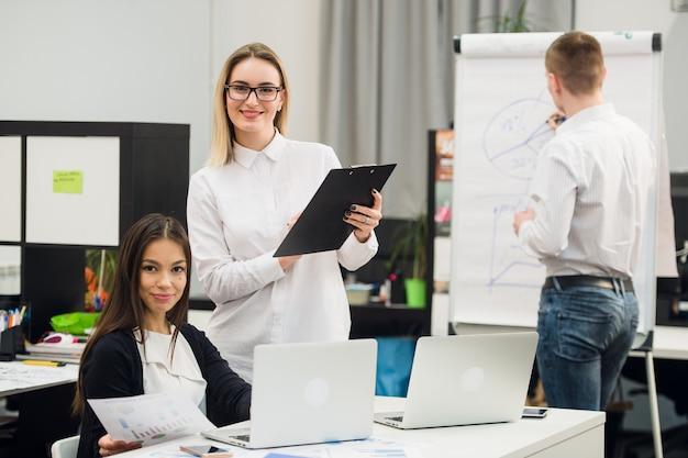 Piękni ludzie biznesu są przyglądającym kamerą i ono uśmiecha się podczas gdy stojący w biurze