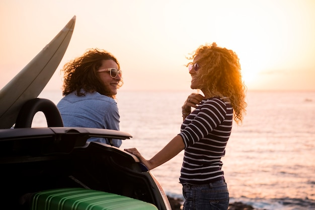 Piękni ludzie para przyjaciół kręcone pani ciesząc się podróżą razem i bawią się przy zachodzie słońca nad oceanem