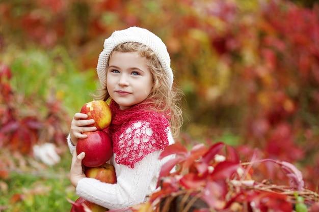 Piękni małej dziewczynki mienia jabłka w jesień ogródzie. . mała dziewczynka bawić się w jabłoń sadzie. berbeć je owoc przy spadku żniwem. zabawa na świeżym powietrzu dla dzieci. zdrowe odżywianie