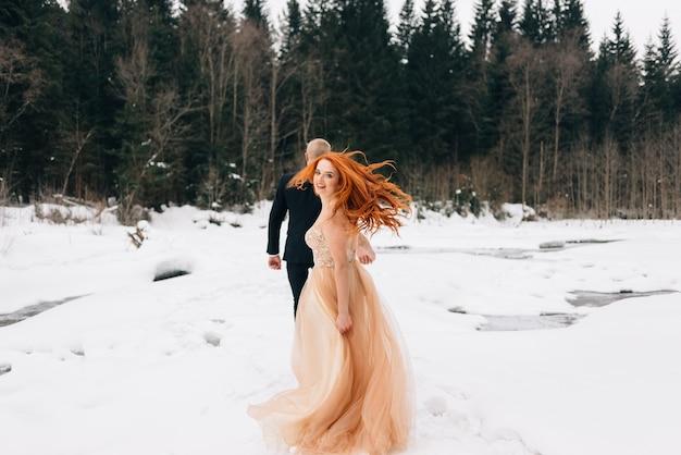 Piękni mężczyźni i kobiety w sukniach ślubnych, wesele zimą.