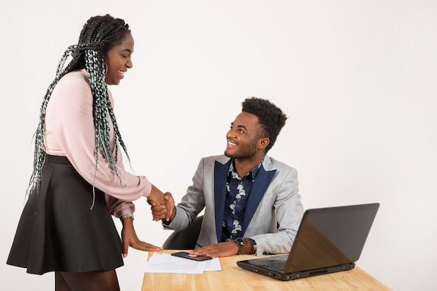 Piękni młodzi afrykańczycy przy stole z laptopem w uścisku dłoni
