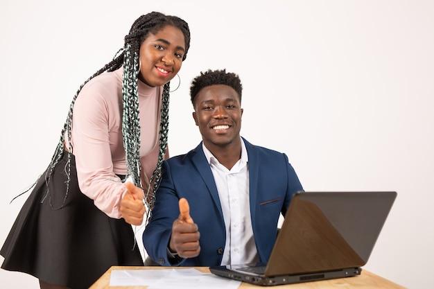 Piękni młodzi afrykańscy ludzie przy stole z laptopem