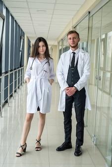 Piękni młodzi lekarze patrzą na aparat w klinice. koncepcja opieki zdrowotnej i medycznej