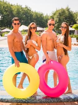 Piękni młodzi ludzie bawią się i piją koktajle.