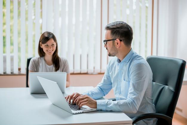 Piękni młodzi partnery biznesowi używają laptop, dyskutują projekt i one uśmiechają się podczas gdy pracujący w biurze.