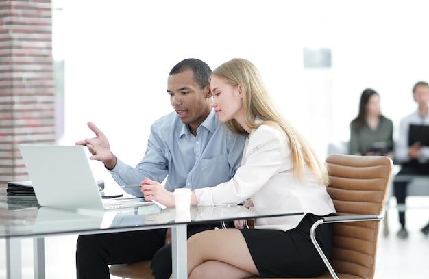 Piękni młodzi partnerzy biznesowi korzystają z laptopa, rozmawiając o dokumentach