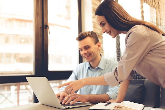 Piękni młodzi partnerzy biznesowi korzystają z laptopa.