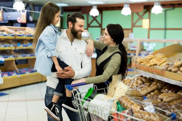 Piękni młodzi rodzice i ich śliczna córeczka uśmiechają się, wybierając pieczenie w supermarkecie