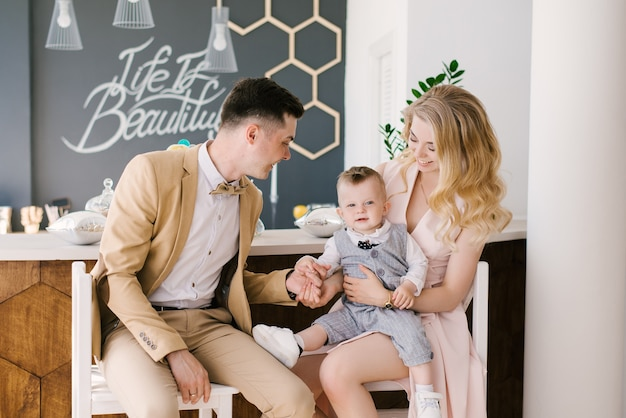 Piękni młodzi rodzice uśmiechają się do swojego jednorocznego dziecka w domu