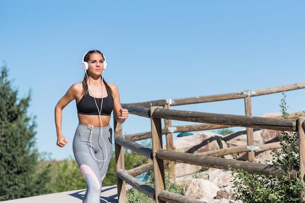 Piękni młodzi sporty kobiety bieg jogging w parku outdoors słucha muzykę