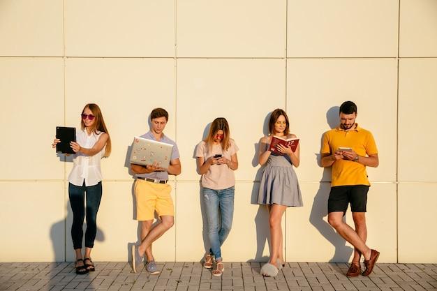 Piękni młodzi ucznie używają gadżety, czytający książkę i ono uśmiecha się