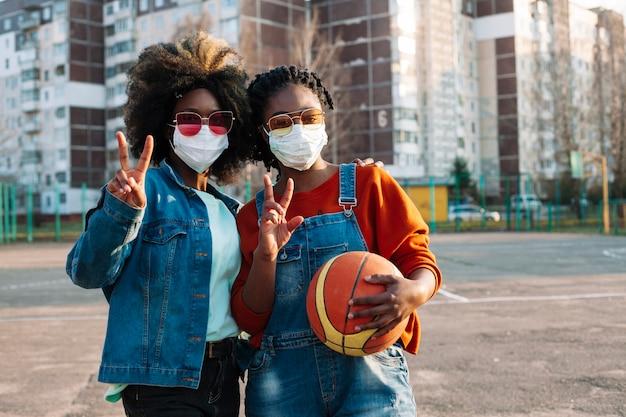 Piękni nastolatkowie pozuje z medycznymi maskami