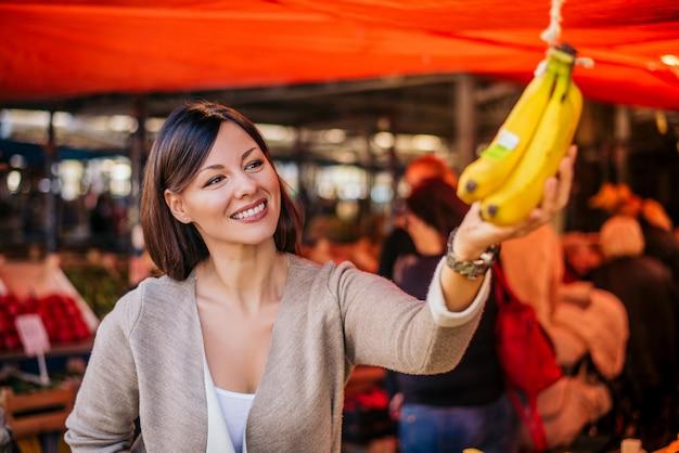 Piękni naturalni brunetki kupienia banany przy zielonym rynkiem.