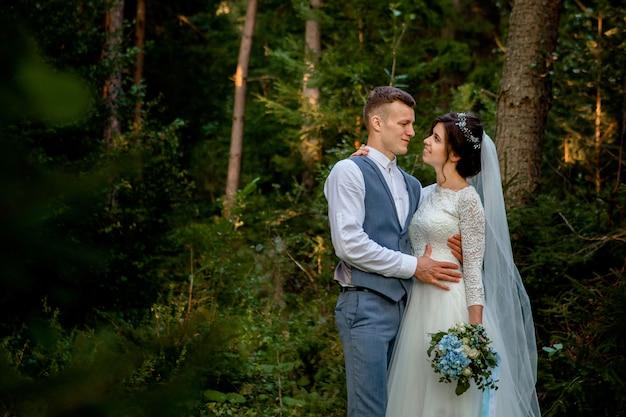 Piękni nowożeńcy pary odprowadzenie w lesie. nowożeńcy. narzeczeni trzymając rękę w lesie sosnowym, zdjęcie na walentynki